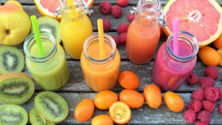 Smoothie in glass jars surrounded by fruits and vegetables